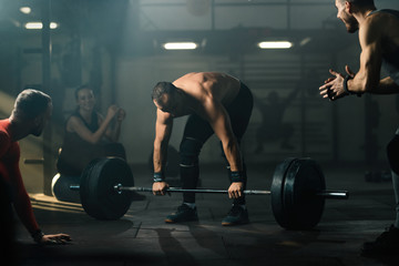 Male athlete exercising deadlift with barbell with support of his friends in a gym.