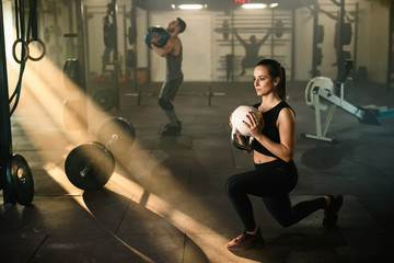 Young sports woman having sports training with kettle bell in health club.