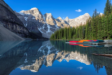 Beautiful sunrise at the Moraine Lake with snow-covered peaks above it in Rocky Mountains, Banff National Park, Canada..