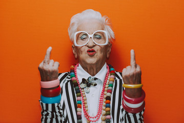 Śmieszne portrety babci. Starszy starsza kobieta ubiera się elegancko na specjalne wydarzenie. modelka babci na kolorowym tle