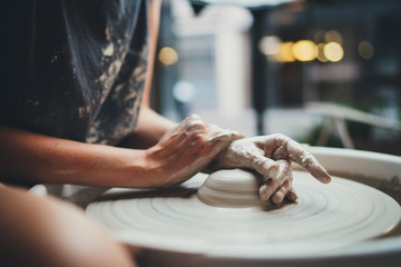 Side View of Young Creative Girl Student Makes her First Vase in a Pottery Class Sitting at a Pottery Wheel in a Cozy Workshop, Handcrafted Product Hobby Art