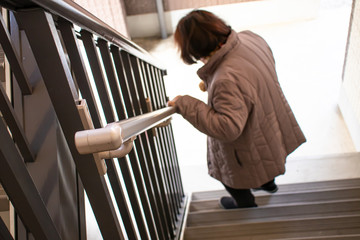 階段を降りている高齢女性