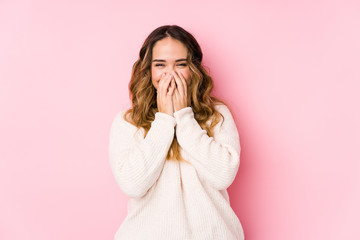 Young curvy woman posing in a pink background isolated laughing about something, covering mouth with hands.