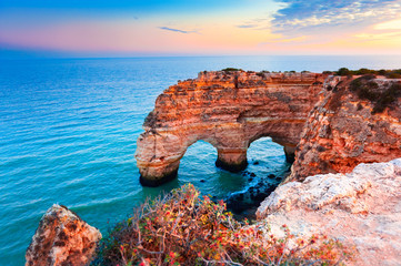 Heart-shaped cliffs on the shore of Atlantic ocean in Algarve, Portugal. Beautiful summer landscape.