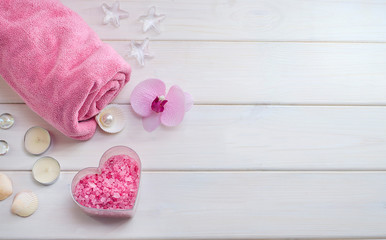 Spa treatments as a gift for Valentine's Day. Pink towel with a flower, shells and pink sea salt in the form of a heart on a white wooden background. Beauty salon