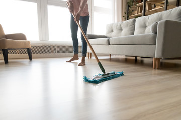 Barefoot woman cleaning floor with wet mop pad cropped image.