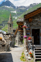 VERTICAL: Empty street leads past a cafe and towards a stone church in the Alps.