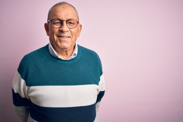 Senior handsome man wearing casual sweater and glasses over isolated pink background with a happy and cool smile on face. Lucky person.