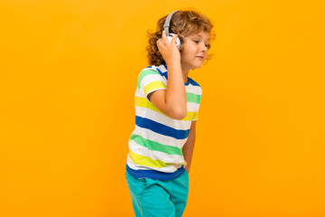 Little boy with curly hair in colourful t-shirt and shorts listen to music with big earphones isolated on yellow background