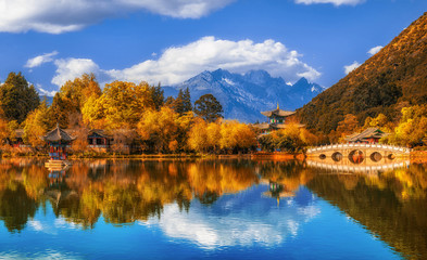 Panorama Landscape view of the Black Dragon Pool at Jade Spring Park with marble bridge over the Jade dragon mountain under blue sky, Lijiang, Yunnan province, China. China culture and travel concept