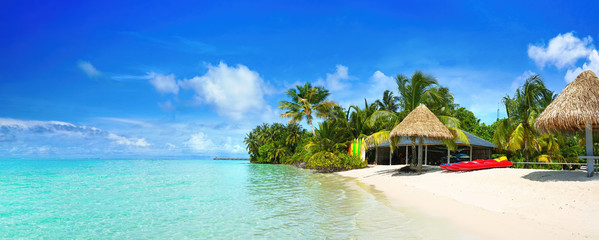 Beautiful beach with white sand, turquoise ocean and blue sky with clouds on Sunny day. Summer tropical landscape with green palm trees and Straw umbrellas, panoramic view.