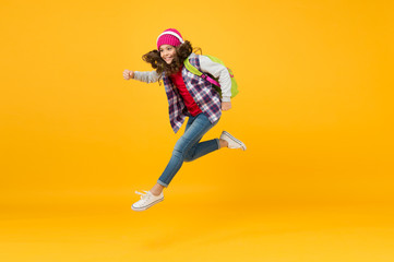 sense of freedom. childhood activity. little girl listen music in headset with backpack. back to school. small schoolgirl running to school. hurry up its holiday time. child being late. energy jump