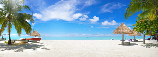 Panorama beautiful beach with white sand, turquoise ocean and blue sky with clouds on Sunny day. Summer tropical landscape with green palm trees and Straw umbrellas with empty copy space.