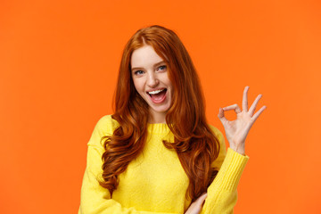 Sassy and daring cool redhead girl with curls, showing okay excellent gesture and smiling excited, assure party be awesome, give permission, say yes, confirm or recommend something, orange background