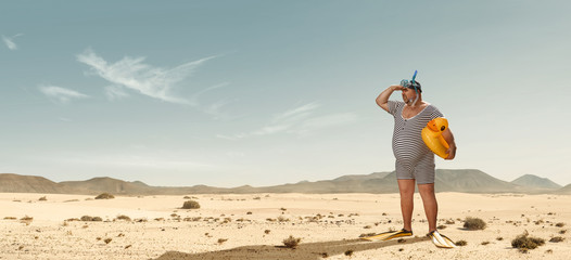 Funny overweight swimmer looking for the beach  in the middle of the desert with copy space