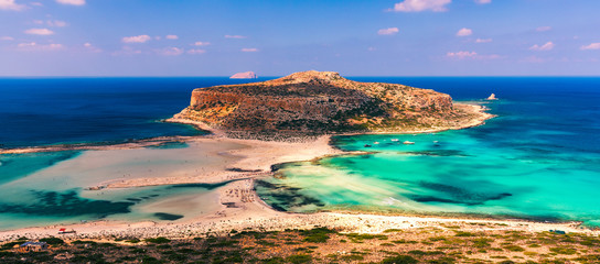 Fantastic panorama of Balos Lagoon and Gramvousa island on Crete, Greece. Cap tigani in the center. Balos beach on Crete island, Greece. Tourists relax and bath in crystal clear water of Balos beach.