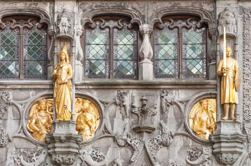 Exquisite golden figures - details of the entrance to Roman Catholic Basilica of Holy Blood in Burg square, Bruges, Belgium