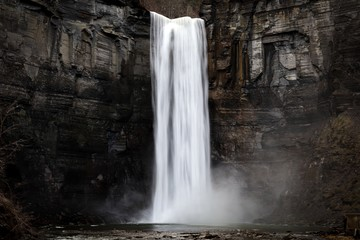 taughannock falls a silky smooth waterfall against a rock face cliff with splashing water at its base