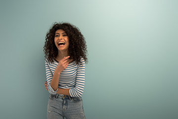 excited bi-racial girl laughing while pointing with finger on grey background