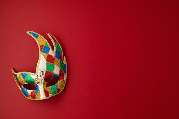 Festive, colorful mardi gras or carnivale mask and accessories over red background. Party invitation, greeting card, venetian carnivale celebration concept. Flat lay, top view, copy space