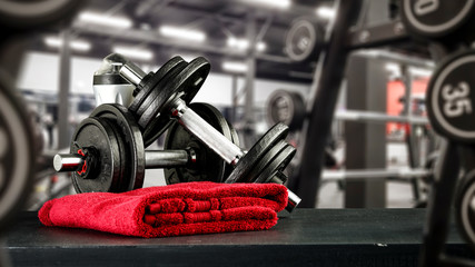 Black desk of free space for your decoration and blurred gym interior.Metal dumbbells and fit life