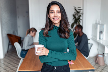 Young indian business woman entrepreneur looking at camera in the office.