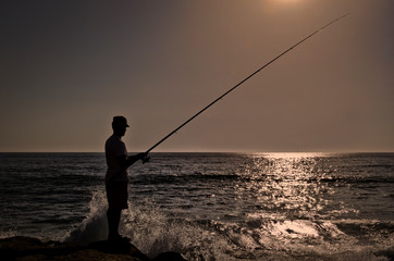Silhouette Of Man Fishing At Sea Against Clear Sky During Sunset
