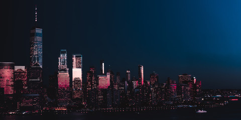 Amazing panorama view on New York City skyline and Downtown Manhattan from Jersey City during night. Banner image