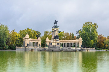 monument to King Alfonso XII, featuring a semicircular colonnade and an equestrian statue of the monarch on the top of a tall central core near the lake in Buen Retiro Park. Madrid, Spain.