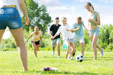 Parents with children playing football on outdoor