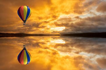 A hot air balloon over a lake at sunrise