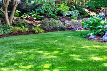 This beautiful backyard woodland garden features a maintenance free lawn made of natural looking artificial grass, a huge landscaping trend for small spaces.