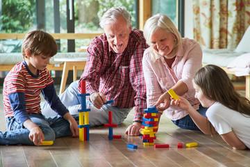 Großeltern stapeln Bauklötze mit Enkelkindern