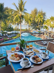 luxury hotel with breakfast table and a look at the swimming pool and ocean in Thailand
