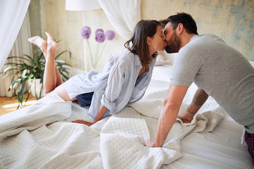 young sexy couple in underwear having a kiss in bed in the morinig on valentines day. Intimacy, passion, erotic concept.