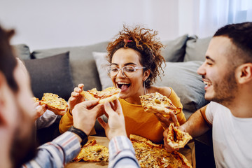 Group of friends sitting on the floor in living room, drinking beer and eating pizza. House party. Man feeding his girlfriend.