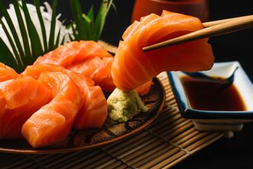 Sashimi, Salmon, Japanese food chopsticks and wasabi on the wood table