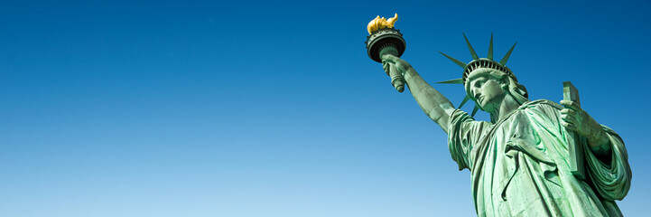 Statue of Liberty in New York, USA. Blue sky panoramic background with copy space