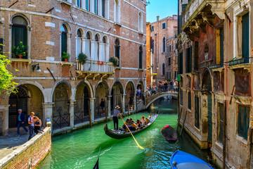 Wąski kanał z gondolą i mostem w Wenecja, Włochy. Architektura i punkt orientacyjny Wenecji. Przytulny pejzaż Wenecji.