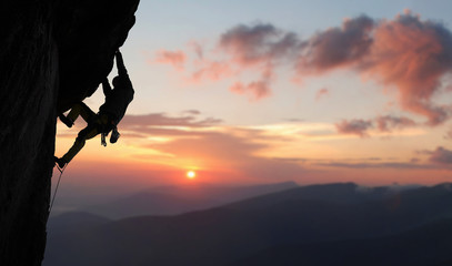 Male climber in rock climbing equipment, pulling up and doing next step on high cliff reaching rocky top. Side view. Panoramic view of mountains and amazing pink sky with sunset and clouds. Copy space