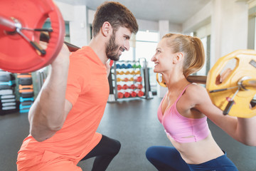 Couple of woman and man in the gym with weights in competition