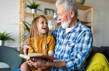 Cute grandfather and beautiful grandchildren reading a book