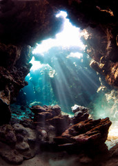 Underwater world. A cave under water permeated with rays of sunlight.