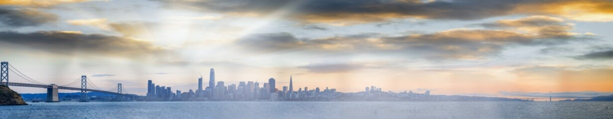 Sunset panoramic view of San Francisco. City skyline over the water