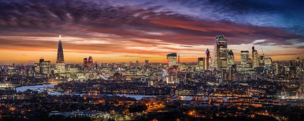 Weites Panorama der beleuchteten Skyline von London am Abend mit den Wolkenkratzern der City und zahlreichen Touristen Attraktionen, Großbritannien