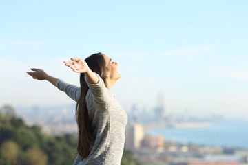 Happy woman stretching arms breathing fresh air outdoors