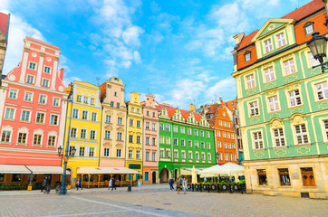 Row of colorful traditional buildings with multicolored facades and street lamp on cobblestone Rynek Market Square in old town historical city centre of Wroclaw, blue sky background, Poland