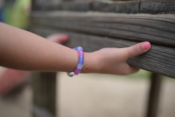 A kid's hands holding on to a bench