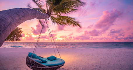 Tropical sunset beach background as summer landscape panorama with beach swing or hammock and white sand and calm sea beach banner. Perfect beach scene vacation or summer holiday concept