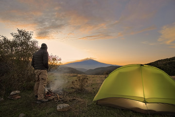 Man Looking Etna Mount By His Illuminated Tent At Sunrise, Sicily